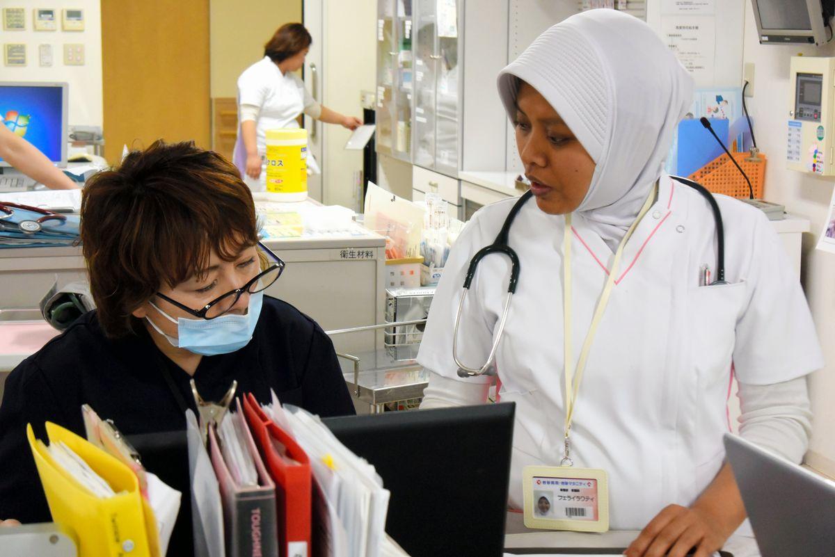 写真・図版 : 日本人と一緒に働く外国人看護師=2017年3月21日、岐阜市