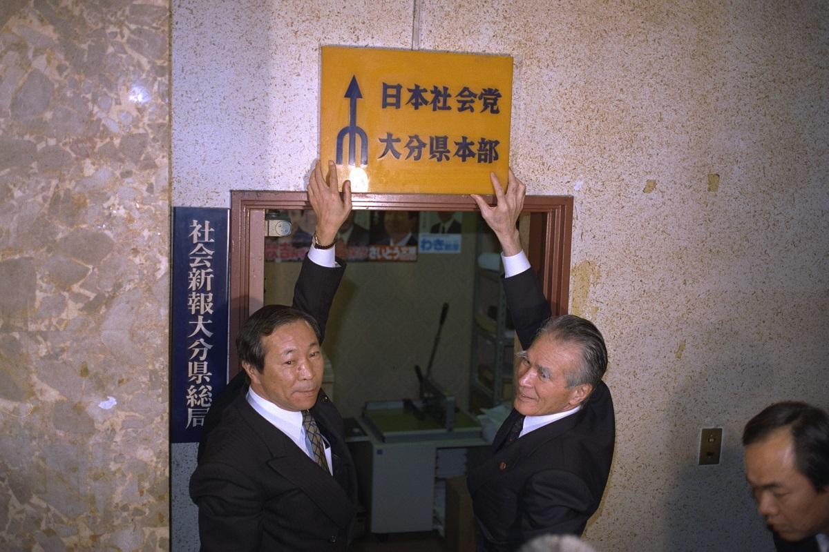 写真・図版 : 社民党に改称し、社会党大分県本部の看板を下ろす当時の村山富市党首(右)=1996年2月29日