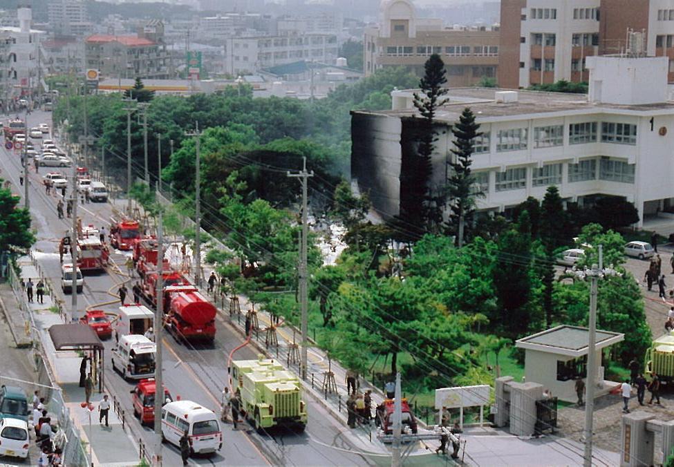 写真・図版 : 15年前、米軍ヘリが墜落して黒く焼け焦げる沖縄国際大の校舎=2004年8月13日、沖縄県宜野湾市提供