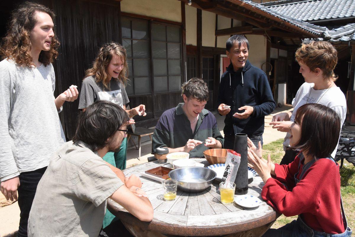 写真・図版 : 滞在する外国人たちと餅を食べながら談笑する日本人夫妻=2019年4月18日午前11時53分、吉備中央町上野、華野優気撮影