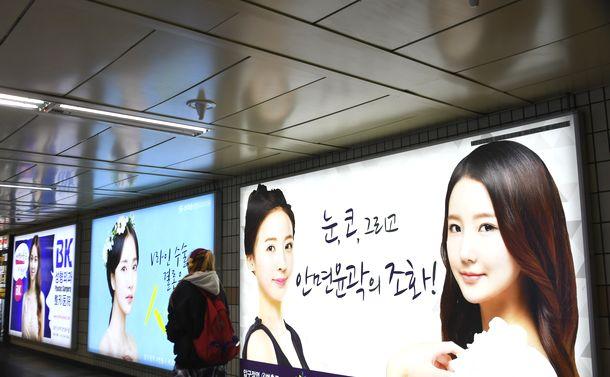 写真・図版 : ソウル市江南(カン・ナム)区の地下鉄新沙(シン・サ)駅に掲げられた美容整形の広告。手前の広告には「目、鼻、そして顔の輪郭の調和」と記されている=2017年12月4日