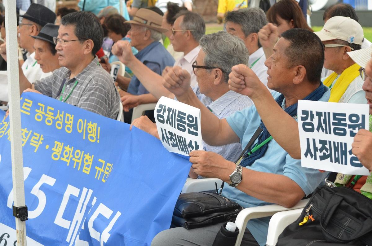 写真・図版 : 8月15日の光復節に開かれた元徴用工の原告を支援する集会。「強制動員 謝罪・賠償」と書かれたプラカードが掲げられた=ソウル市庁前