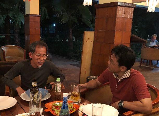 写真・図版 : 宿舎1階のオープンエアのレストランで食事をしながら野球哲学を語り合うイマニ(左)と著者。肌には防蚊スプレーをたっぷりかけ、足元には蚊取り線香と、万全のマラリア対策を施している。