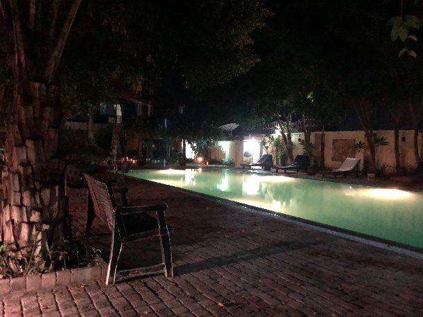 写真・図版 : リゾート地かと思わせる雰囲気を醸すライトアップされた夜のプールだが、水は濁って底が見えない。電気は宿舎の発電機から供給されている。