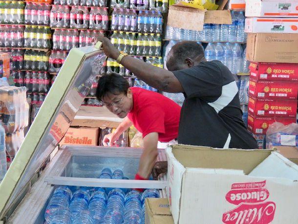 写真・図版 : ジュバ大学に向かう途中、スーパーに立ち寄りペットボトルの水を購入する。冷えているボトルを選ぶとき、すっかり顔なじみのお店のご主人が手伝ってくれる。