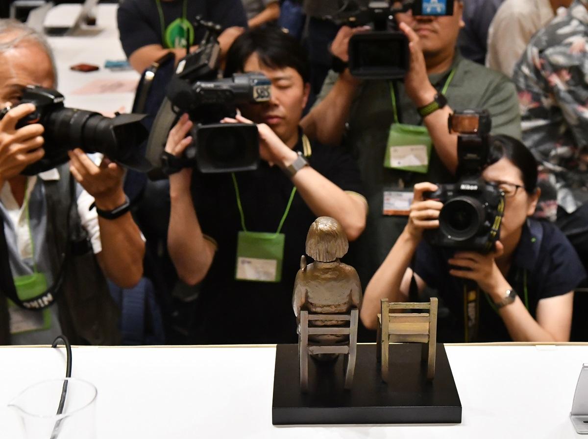 写真・図版 : あいちトリエンナーレの「表現の不自由展・その後」中止問題を受けた記者会見で、会場に置かれた少女像のミニチュアを撮影するカメラマンたち=2019年9月2日、東京都千代田区