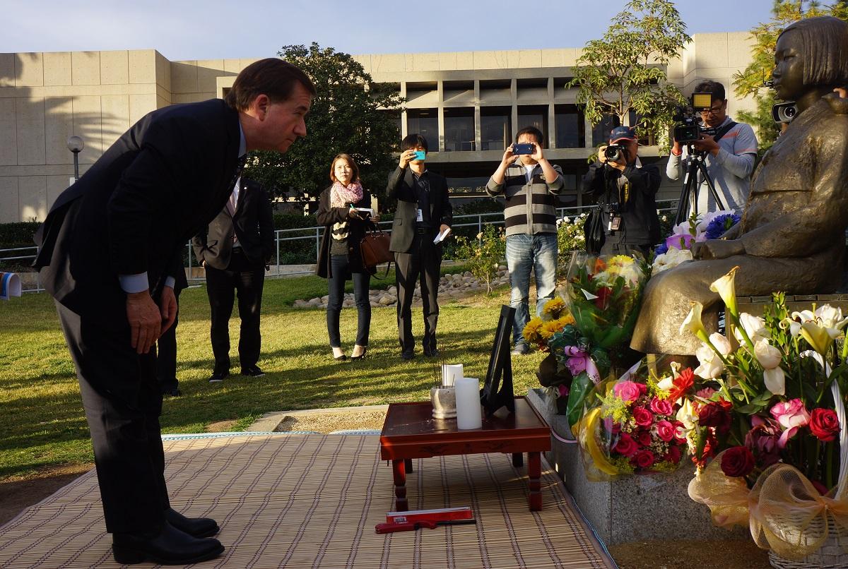 写真・図版 : 米グレンデール市に設置された少女像におじぎするエド・ロイス米下院外交委員長=2014年1月31日