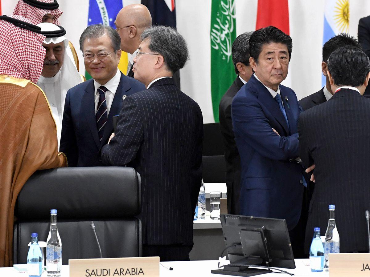 写真・図版 : G20サミットの会議の前に韓国の文大統領(左側中央)と握手した後、開会を待つ安倍首相(右側中央)=6月、大阪市。代表撮影