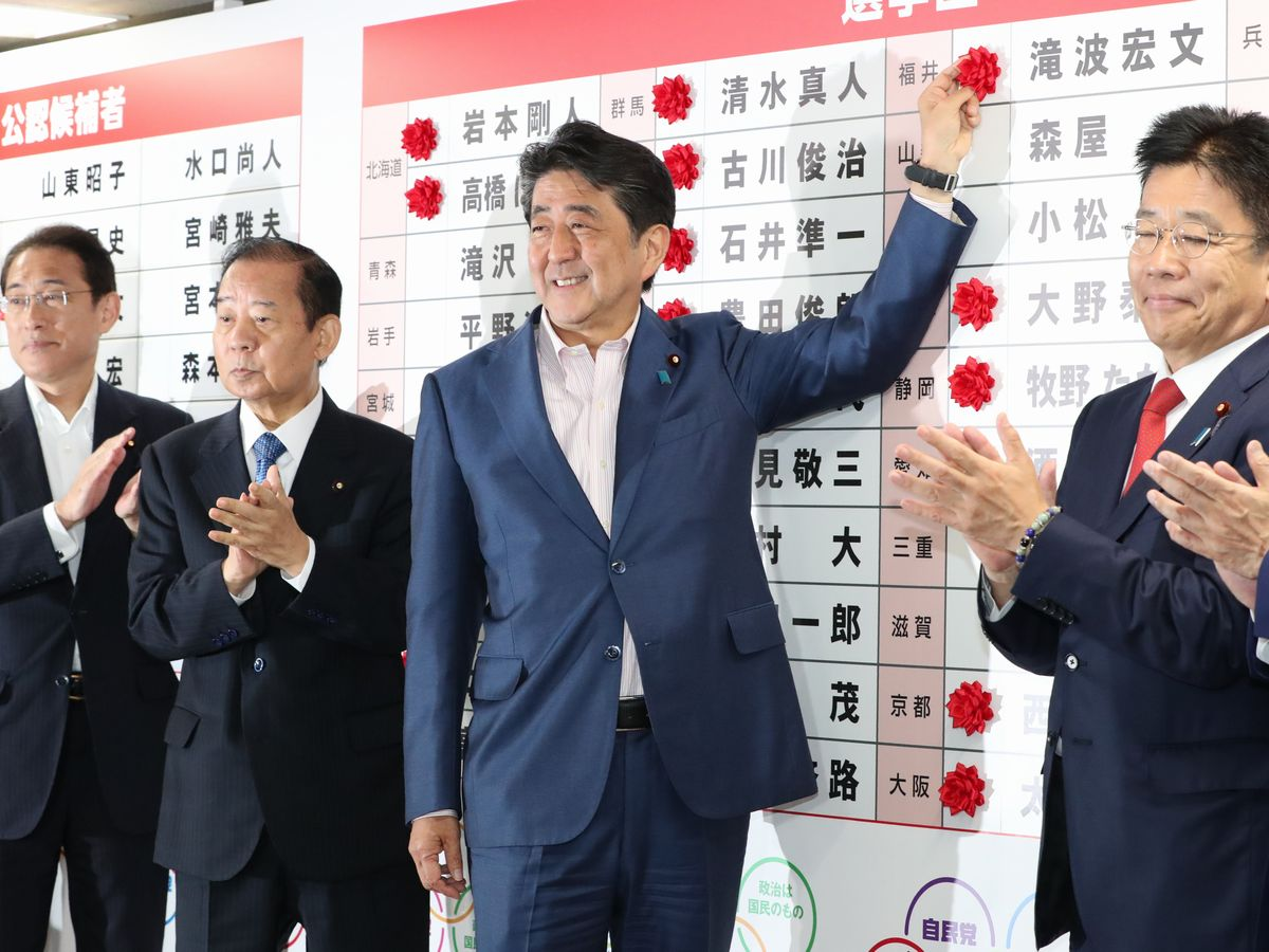 写真・図版 : 7月21日、参院選で当選者の名に花をつける安倍首相=自民党本部。朝日新聞社