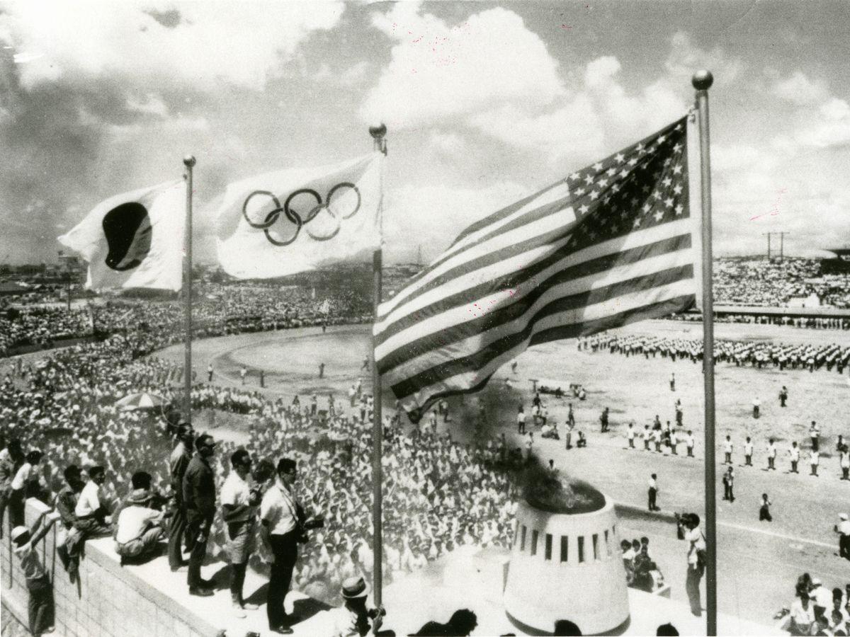 写真・図版 : 東京五輪のあった1964年9月、米軍統治下の沖縄でも日米両国旗の下に聖火が燃えた=那覇市の奥武山競技場。朝日新聞社