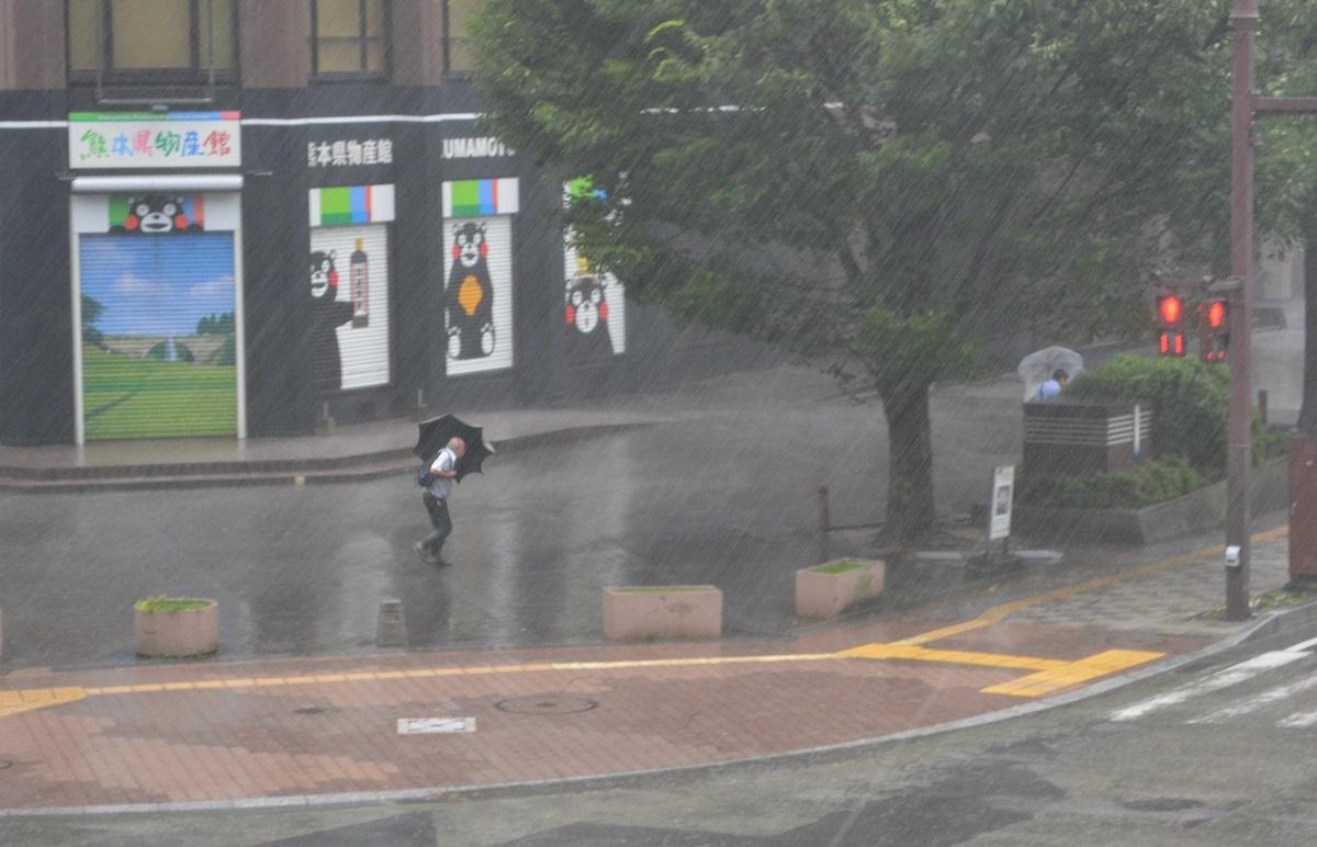 写真・図版 : 台風8号が接近、横殴りの雨の中を傘をかしげて通勤する人=2019年8月6日、熊本市