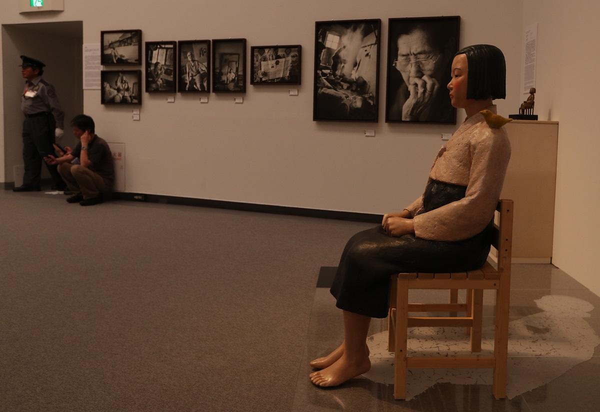 写真・図版 : 「あいちトリエンナーレ2019」の「表現の不自由展・その後」に一時出展された「平和の少女像」と元慰安婦の写真=愛知芸術文化センター