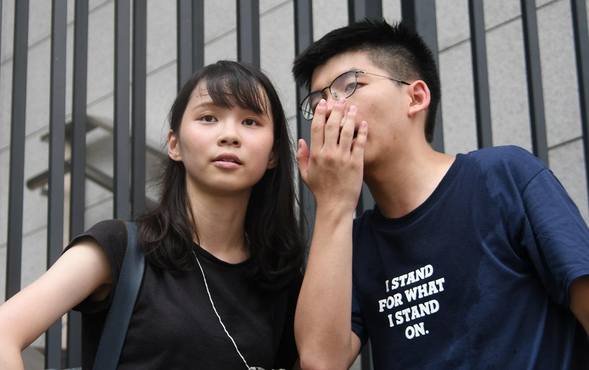 写真・図版 : 一時拘束された黄之鋒氏(右)と周庭氏=2019年6月