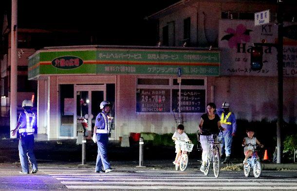 写真・図版 : 停電で信号がつかず、手信号で通行者を誘導する警察官=2019年9月11日午後6時33分、千葉市緑区
