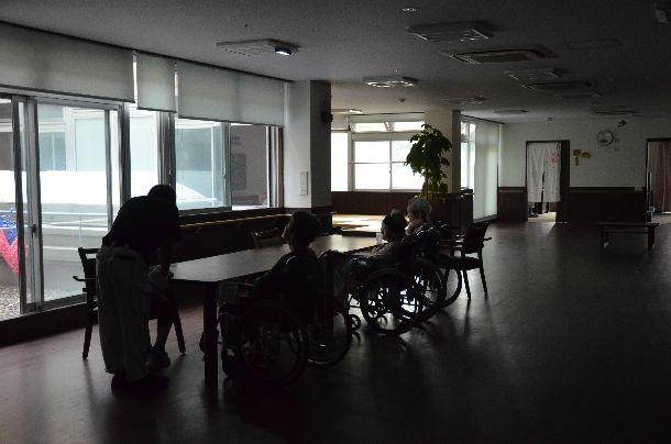 写真・図版 : 停電のため、非常灯をつけても暗いリビングで過ごす特養の入所者ら=2019年9月11日午後5時40分、千葉県君津市