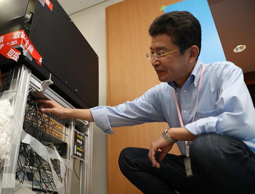 写真・図版 : 東京スカイツリーの上と下で時間の流れに差があるかの検証実験に入る前の光格子時計(左)と東京大の香取秀俊教授=2018年10月2日、東京都墨田区、池田良撮影