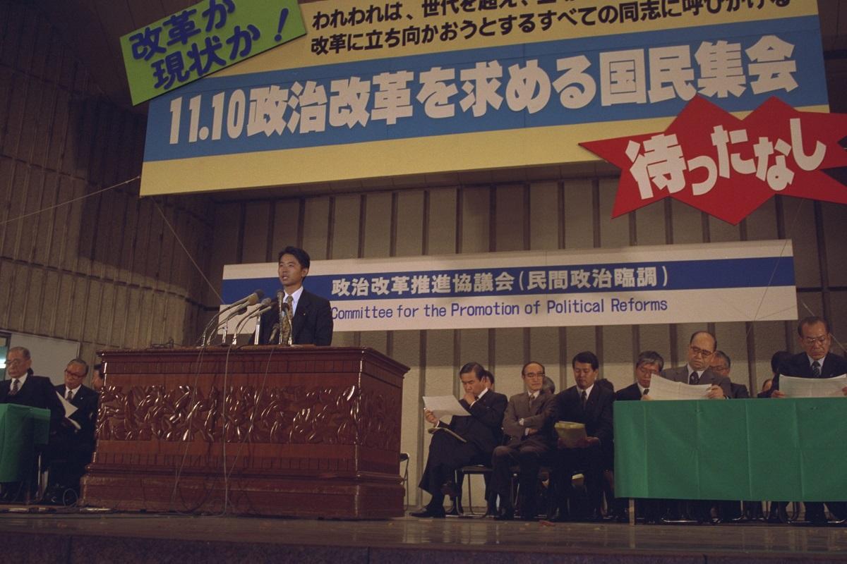 写真・図版 : 民間政治臨調主催の「政治改革を求める国民集会」。共産党を除く当時の与野党の国会議員188人が署名した衆議院中選挙区制度の「廃止宣言」が、自民党の赤城宗彦議員によって読み上げられた=1992年11月10日、東京・日比谷