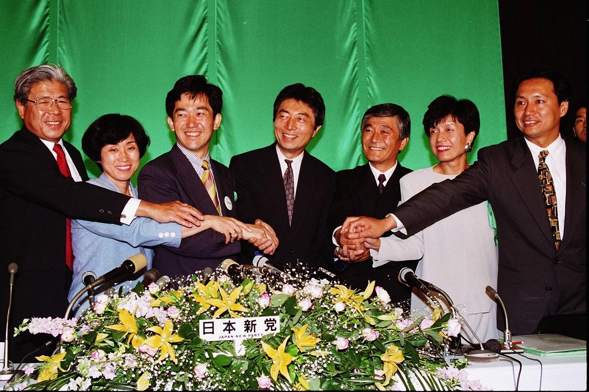 写真・図版 : 初挑戦の衆院選で躍進し、党本部で当選者たちと握手する日本新党の細川護熙代表(中央)=1993年7月19日、東京都港区