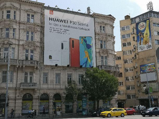 写真・図版 : 中国の華為技術(ファーウェイ)のスマホの広告。華為はハンガリーにも拠点を持ち、同社のスマホも人気がある。米国の同社への批判を気にする消費者は少ない=2019年7月19日、ブダペスト、吉岡桂子撮影