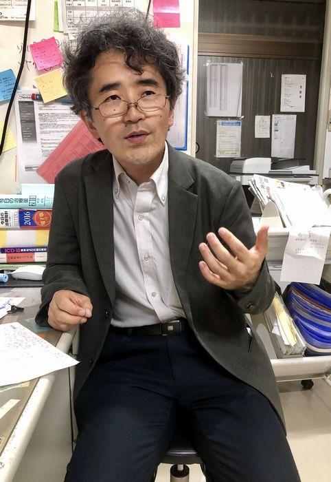 写真・図版 : ことぶき共同診療所の診察室で語る越智祥太さん