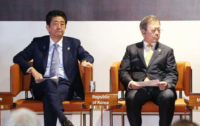 写真・図版 : ポートモレスビーで開かれたAPECビジネス諮問委員会(ABAC)に臨む安倍晋三首相(左)と韓国の文在寅大統領=2018年11月17日、代表撮影