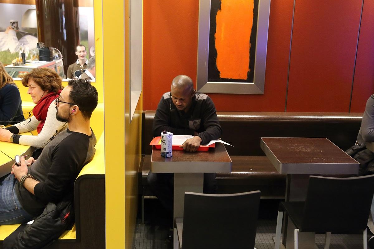 写真・図版 : 高山明さんがフランクフルトで開催したプロジェクト『マクドナルドラジオ大学』。参加者はマクドナルドの店内で、難民の講義をラジオのイヤホンで聴く=2017年、photo: Masahiro Hasunuma