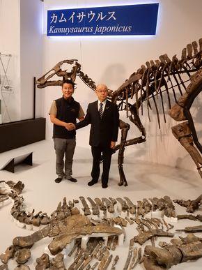 写真・図版 : 学名「カムイサウルス」の発表に臨んだ小林快次・北大教授(左)と竹中喜之・むかわ町長。手前に実物化石、後ろに復元骨格がある=国立科学博物館、筆者撮影