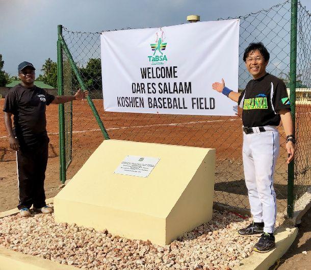 写真・図版 : 野球場の名称は、ダルエスサーム甲子園球場。レフトのファウルグラウンドに出入り口をつくり、バナーを設置。記念碑も設置された。左はンチンビ事務局長。