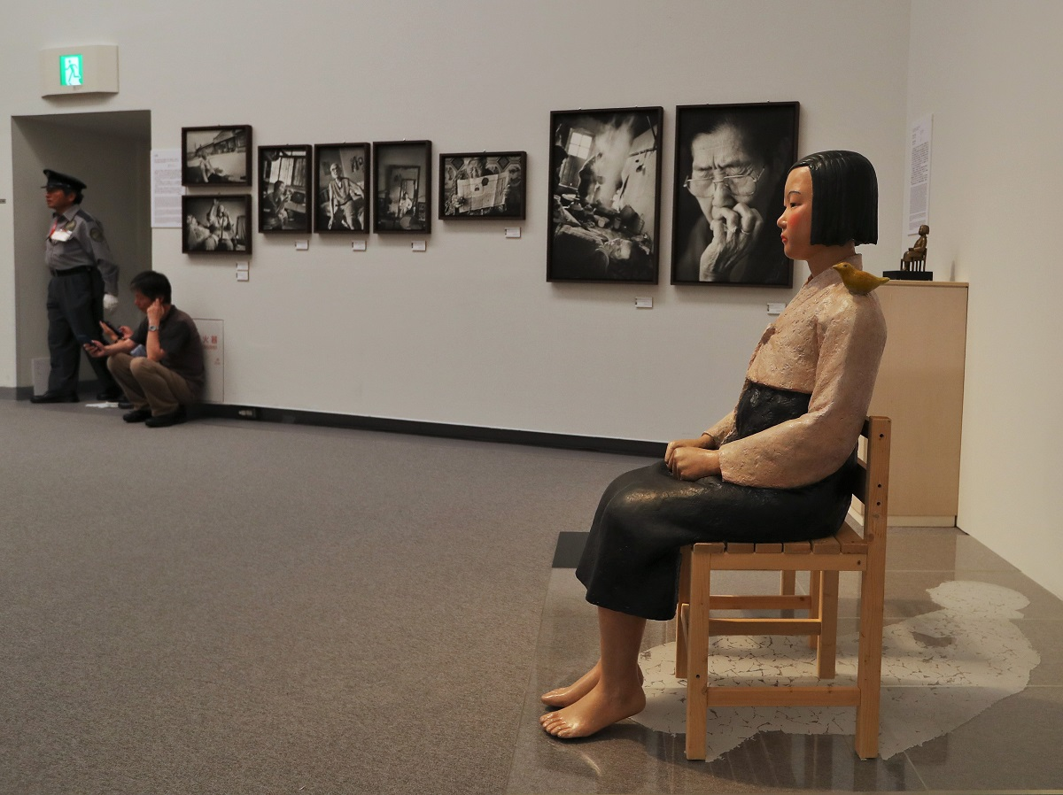 写真・図版 : 「表現の不自由展・その後」に出展された「平和の少女像」と元慰安婦の写真=2019年7月31日、名古屋市東区の愛知芸術文化センター