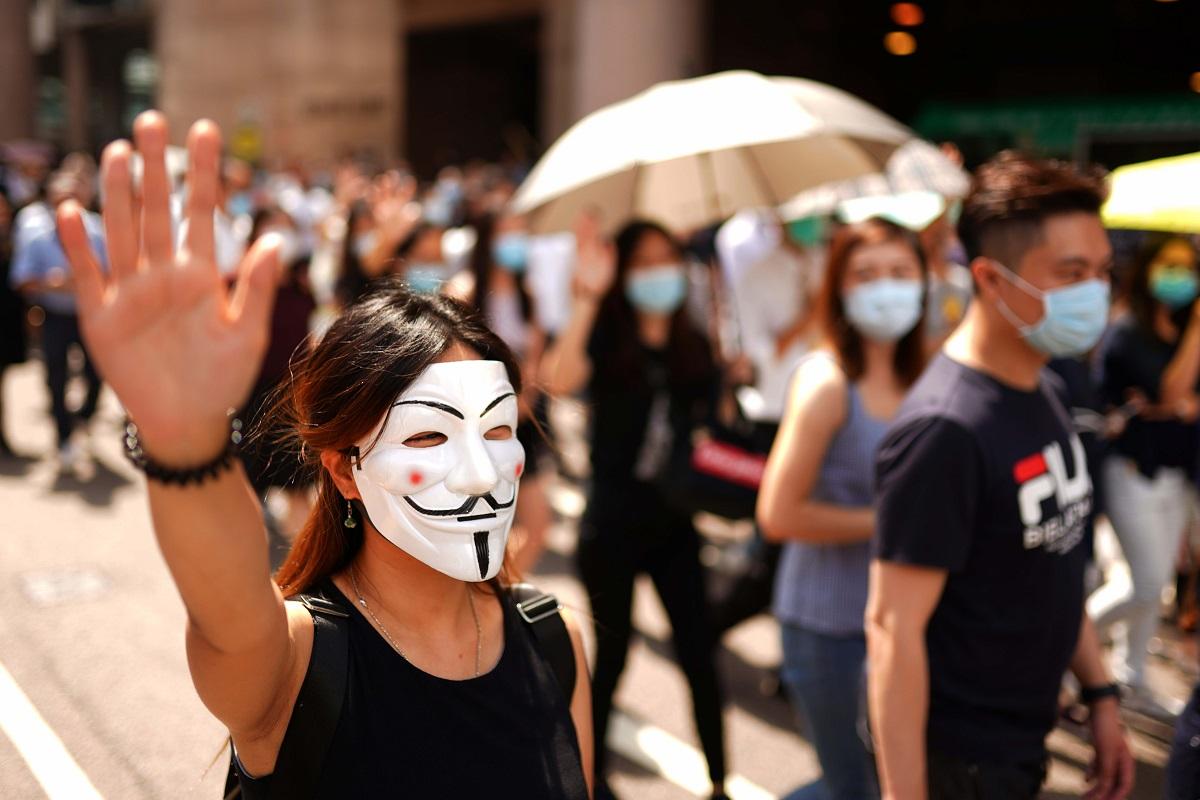 写真・図版 : 覆面禁止法に反対するデモ隊。多くの参加者が顔を隠すマスクなどをして声を上げた=2019年10月4日、香港