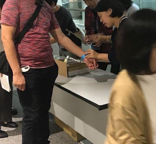 写真・図版 : 「不自由展」の抽選受け付けで番号付きの青いバンドを腕に付ける人たち(奥)=2019年10月8日、愛知芸術文化センター(筆者撮影)
