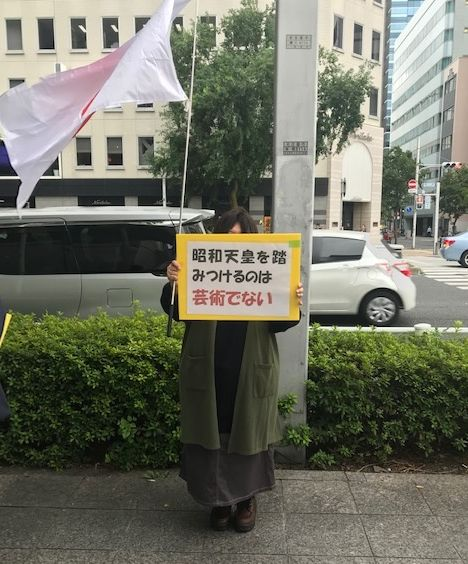 写真・図版 : 会場の外でプラカードを持ち再開に異議を唱える女性=2019年10月8日、愛知芸術文化センター前(筆者撮影)