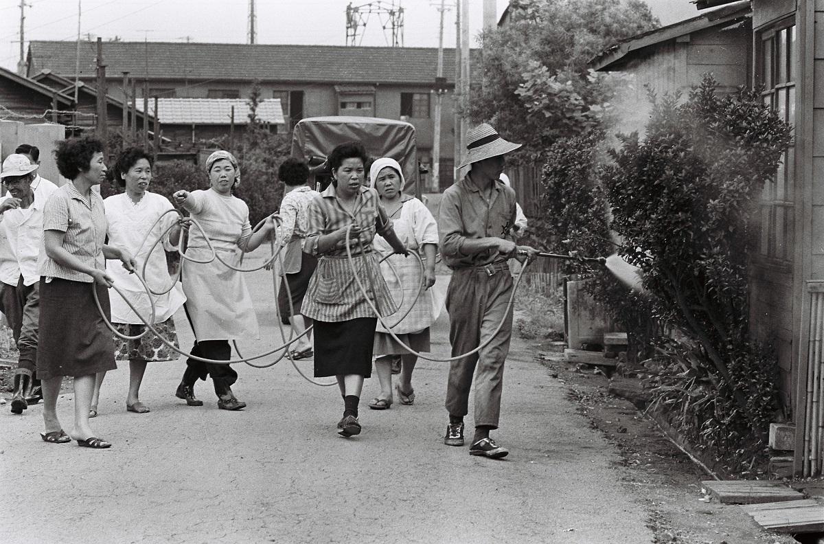 写真・図版 : 「ポリオ流行地」となった東京・足立区大谷田町は当時「恐怖の地区」と報道された。町内の消毒は近所の主婦も手伝った=1961年6月