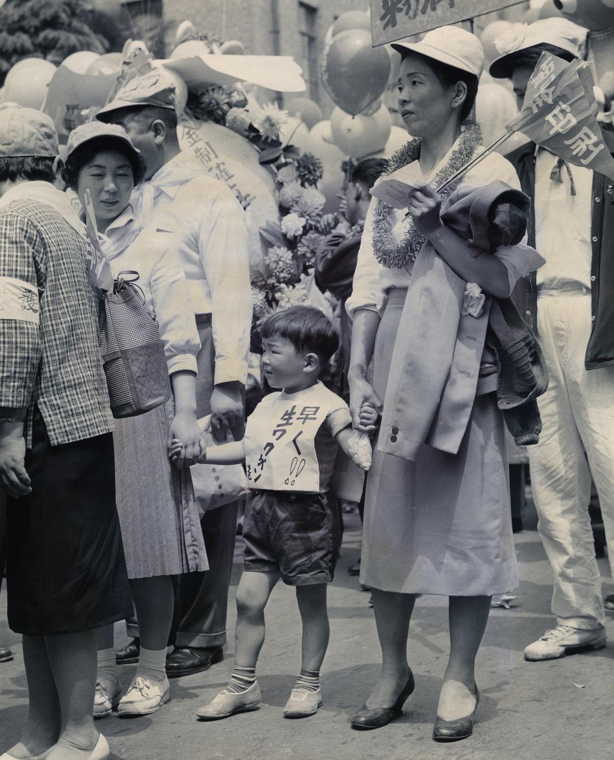 写真・図版 : 1961年5月のメーデーで、生ワクチンの配布を訴える子ども。「早く!! 生ワクチン」の文字が見える