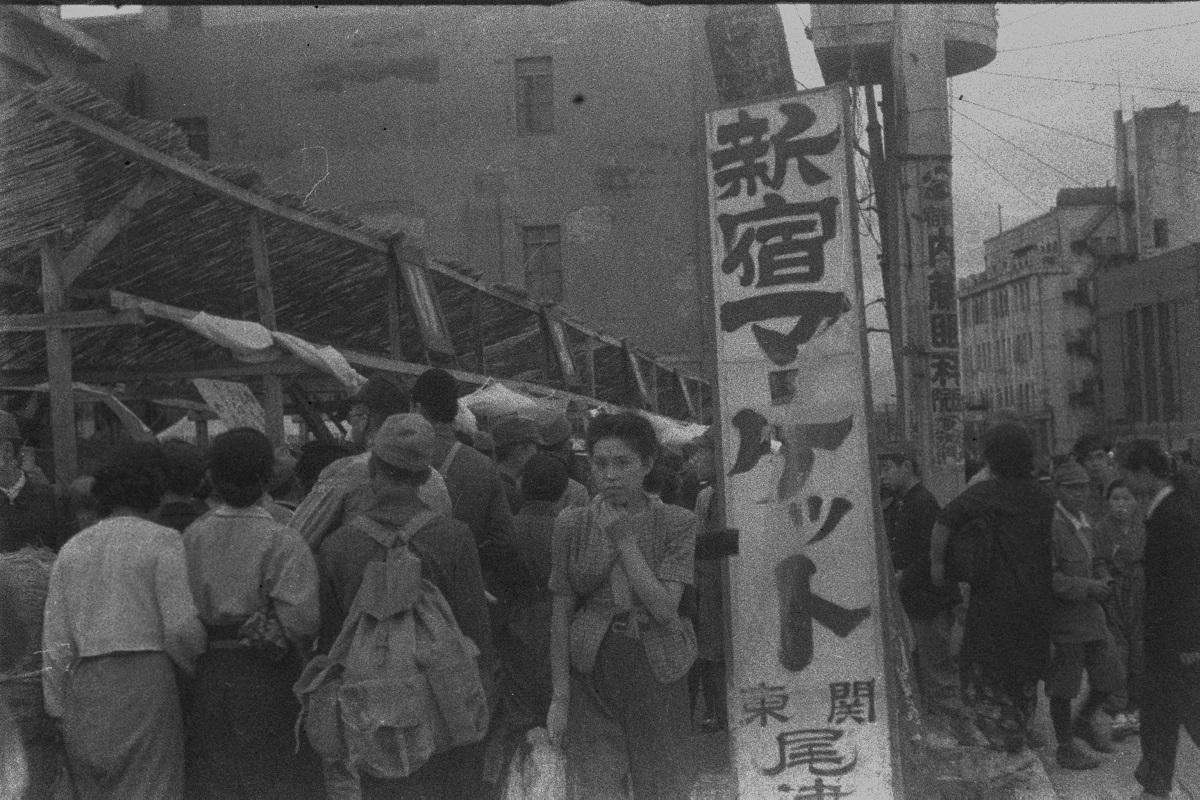 写真・図版 : 1945年(昭和20)10月の東京・新宿。空襲に焼かれ廃墟が目につく中にも、露店が軒を並べ、商店街には復興の兆しが。よしず張りの「新宿マーケット」には日用品が並べられ、飛ぶように売れていた