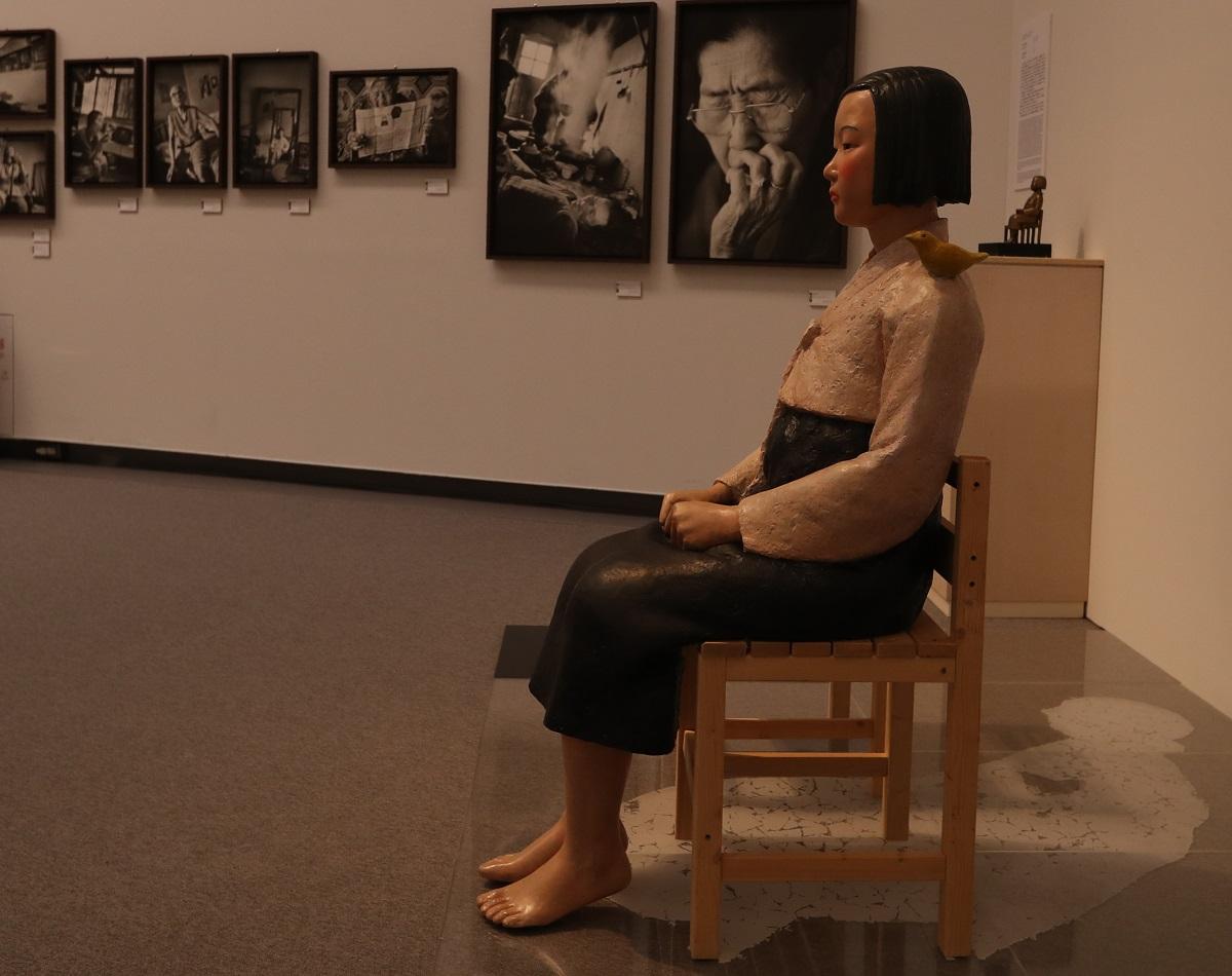 写真・図版 : 「表現の不自由展・その後」に出展された「平和の少女像」と元慰安婦の写真