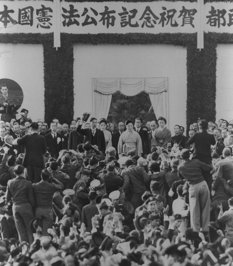 写真・図版 : 「日本国憲法公布祝賀都民大会」に集まった人々に、帽子を振って応える昭和天皇=1946年11月3日、東京・皇居前広場