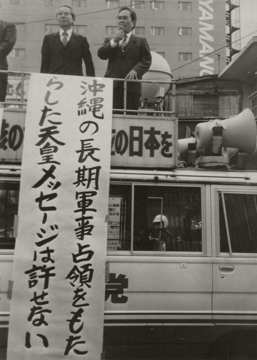 写真・図版 : 昭和天皇の「沖縄メッセージ」を批判する那覇市の街頭宣伝。昭和天皇は宮内庁御用掛だった寺崎英成を通じてアメリカに対し「沖縄を始め琉球の他の諸島を軍事占領し続けることを希望している」というメッセージを伝えていた=1989年1月12日、那覇市国際通り