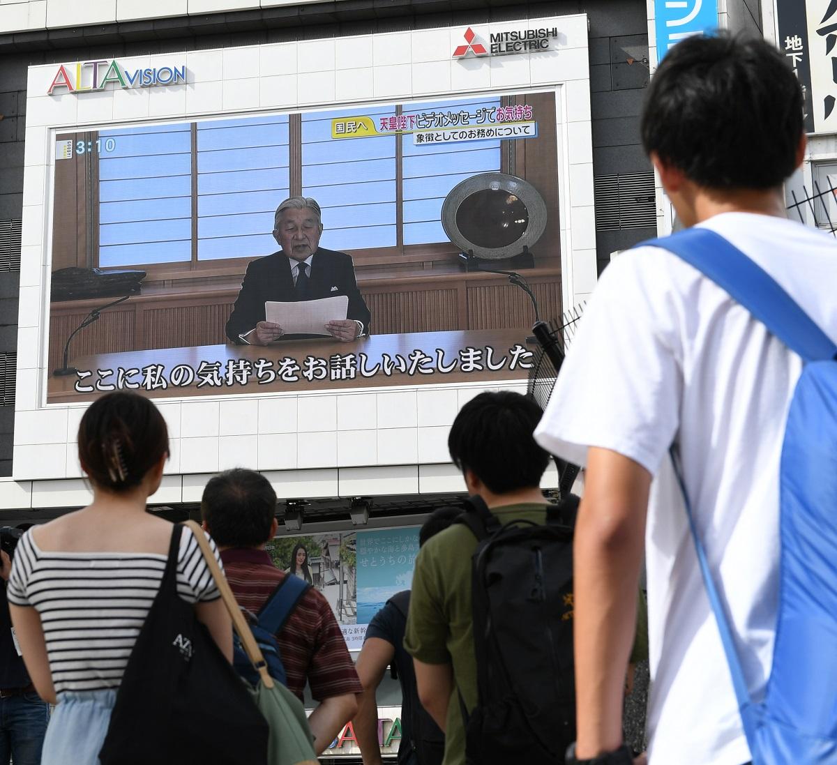 写真・図版 : 生前退位を希望する天皇のビデオメッセージを見上げる人々=2016年8月8日、東京・新宿