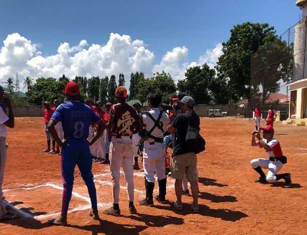 写真・図版 : 熱戦の様子を試合前からカメラに収めるアフリカ野球友の会学生部リーダー高橋海輝さん。