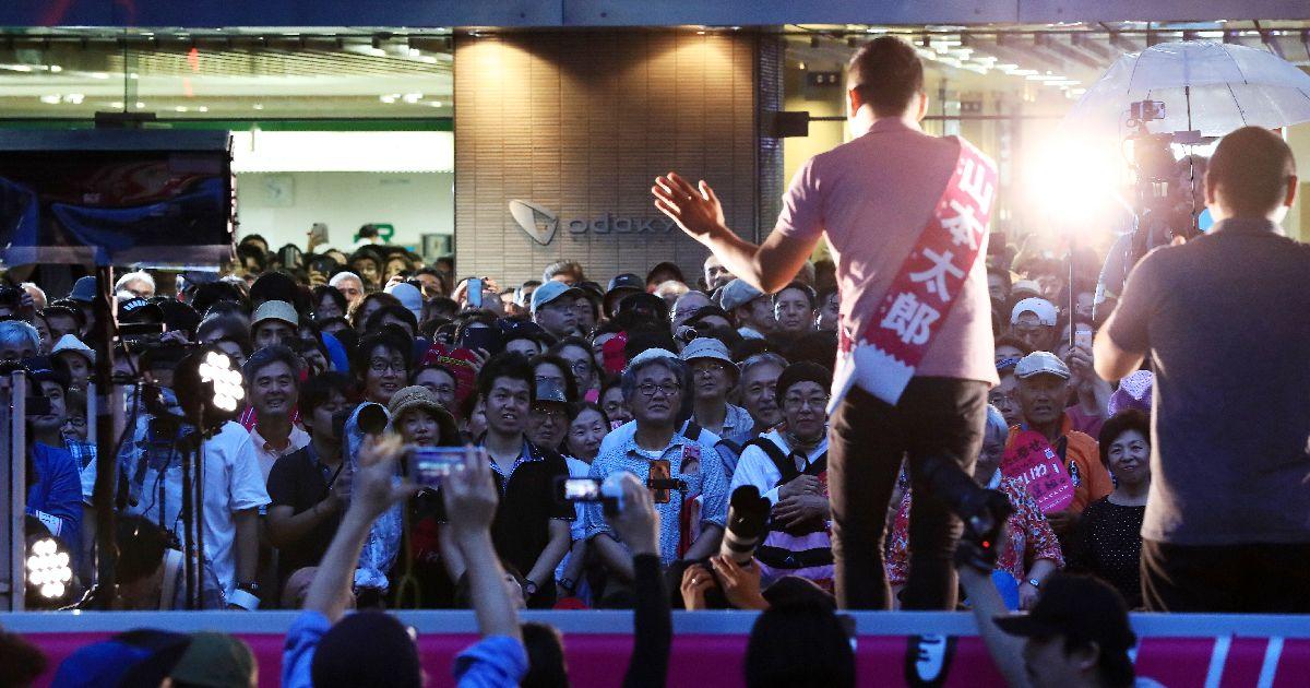 写真・図版 : 7月の参院選投開票日前夜、山本太郎代表(手前)ら「れいわ新選組」候補者が「最後の訴え」をした新宿駅前は大勢の人たちで埋まった=2019年7月20日