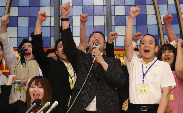 写真・図版 : 比例区での当選を決め、関係者と「NHKをぶっ壊す!」と叫ぶNHKから国民を守る党の立花孝志代表(中央)=2019年7月22日、東京都港区