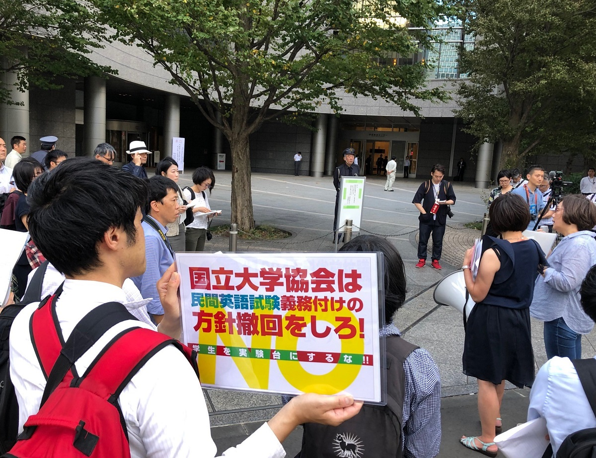 写真・図版 : 英語民間試験の導入に反対し、国立大学協会が入るビルの前で抗議行動をとる市民ら=2019年10月4日、東京都千代田区