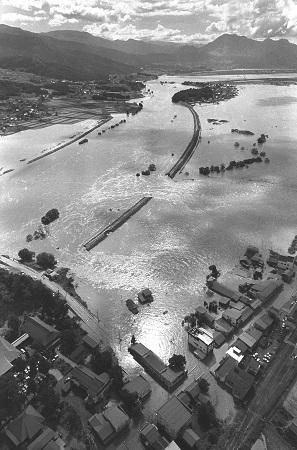 写真・図版 : 千曲川の決壊は繰り返されてきた。1983年9月の台風禍の大雨による決壊で、水浸しになった長野県飯山市の住宅地=朝日新聞社ヘリから、朝日新聞写真部撮影