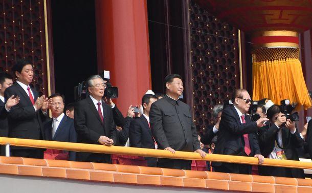 写真・図版 : 習近平国家主席(中央)と並んで軍事パレードを見守る江沢民氏(向かって右)、胡錦濤氏(同左)ら=2019年10月1日、北京
