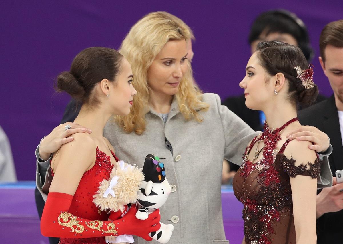 テリ・トゥトベリゼコーチ(中央)から祝福される、金メダルのアリーナ・ザギトワ(左)と銀メダルのエフゲニア・メドベージェワ=23日、江陵アイスアリーナ