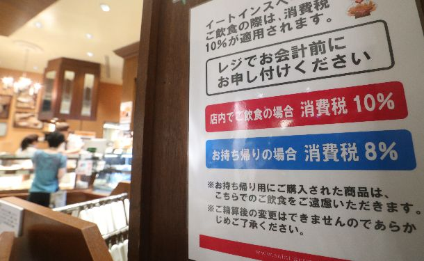 写真・図版 : 飲食スペースを設けているパン屋には、店内での飲食と持ち帰りで税率が異なることを知らせる貼り紙があった=2019年10月1日、東京都千代田区