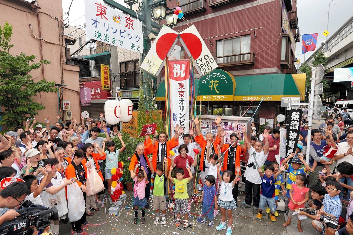 写真・図版 : オリンピックの東京招致が決定、くす玉を割り万歳三唱する商店街の人々=2013年9月8日、東京都板橋区
