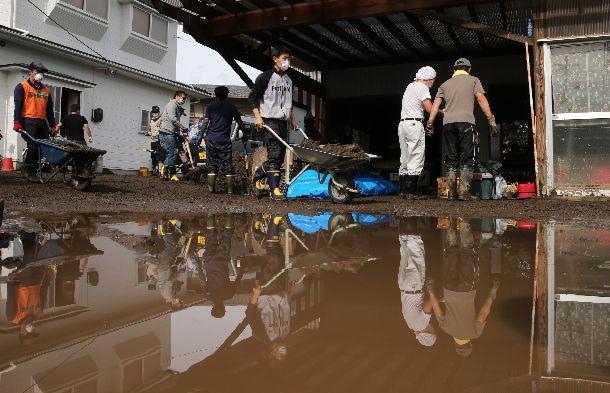 写真・図版 : 水害の被害を受けた住宅から土砂を運び出すボランティアたち=2019年10月20日、宮城県丸森町