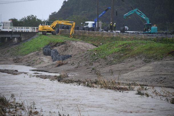 写真・図版 : 宮城県丸森町では雨が降り続く中、決壊した新川の堤防を補強する作業が進められていた=2019年10月22日、宮城県丸森町